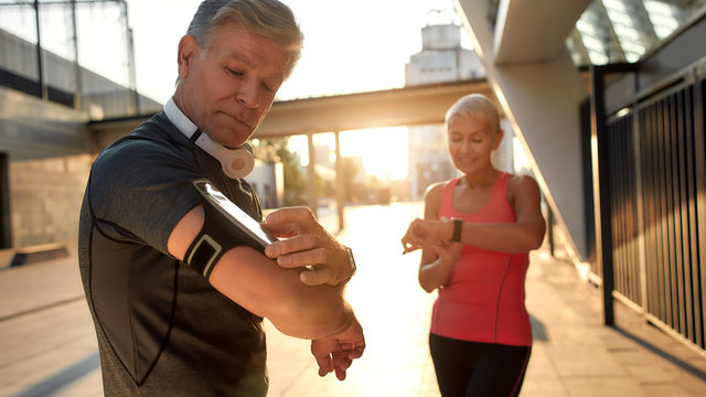Using modern techologies. Active middle-aged couple in sports clothing checking training results while standing together outdoors. Checking pedometer