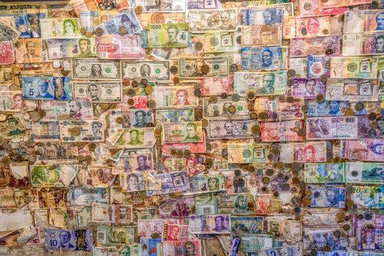 An  assortment money currencies stuck on a wall
