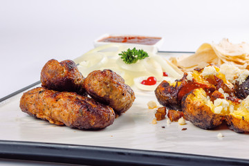 kebab and baked potato with cheese. onion circles and pita bread, red sauce on a white board. great snack dish for beer. close up view