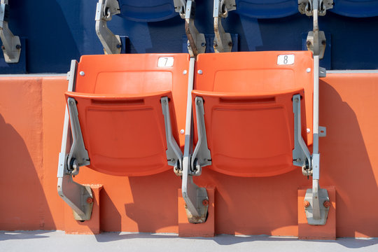 Orange and blue seats from a sports venue waiting to be used