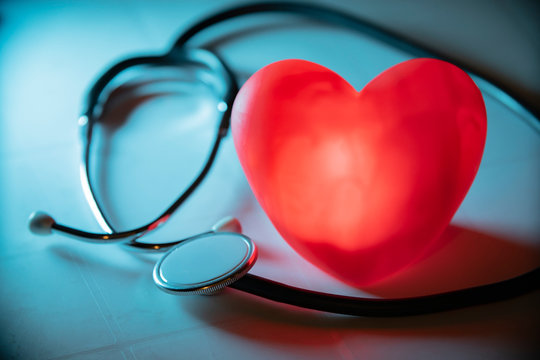 Red heart with stethoscope on blue background. Copy space