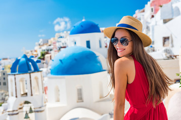 Europe Greece Santorini travel vacation woman on famous santorini Oia island travel destination. Happy young tourist girl in hat and sunglasses relaxing at blue dome church. Summer wanderlust. Fotomurales