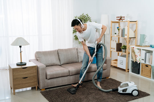 male household cleaning lifestyle concept. young asian chinese man in headphones with vacuum cleaner at home living room tidy up carpet. handsome guy enjoy music in earphones while doing housework.