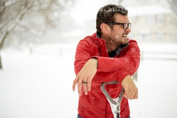 Closeup shot of a male with his hands on the snow shovel and wearing a red jacket on a snowy day
