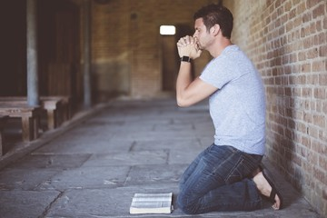Closeup shot of a male on his knees with an open bible in front of his while praying