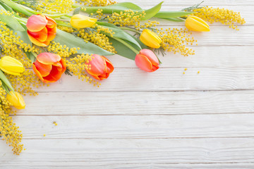 tulips and mimosa on white wooden background Wall mural