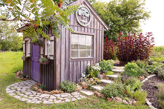 Custom Built Cottage Like Garden Shed with Cobblestone Sidewalk and Wood Board and Batten Siding