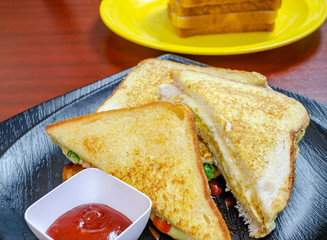 Toasted Bread Sandwiches with ketchup on a black plate with more stacked bread slices in the background.