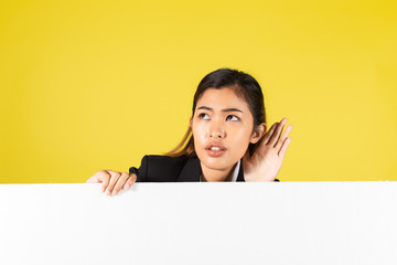 Young Asian female with blank advertisement placard holding hand near ear and listening to gossip against yellow background