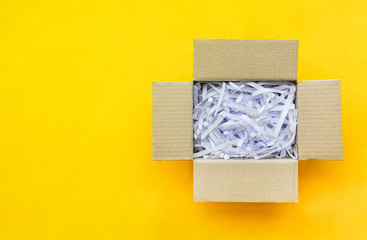 top view reuse shredded paper documents in brown paper cardboard isolated on yellow background with copy space, flat lay