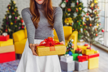 Closeup happiness asian woman wearing colorful red sweaters with hat holding and giving the gift box to other for merry christmas celebration, asian or asean indoors party, xmas and new year concept
