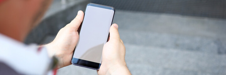 Focus on male hands holding modern cellphone. Man sitting on stairs with sensory mobile phone and messaging with friends. Copy space on screen of gadget. Blurred background