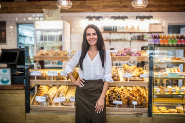 Spoed Fotobehang Bakkerij Cheerful young woman owning bakery feeling excited before starting work