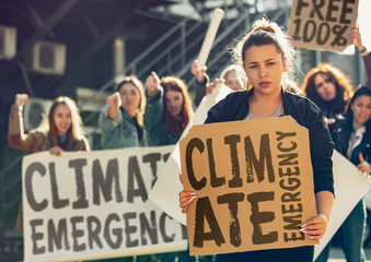Young woman with poster in front of people protesting about climate changing on the street. Meeting about problem in ecology, environment, global warming, industrial influence, climate emergency.