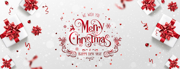 Fototapete - Red Christmas and New Year Text on Xmas background with gift boxes, red ribbon, decoration, sparkles, confetti