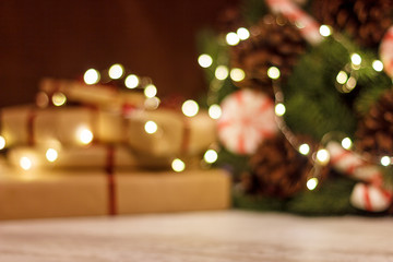 Fototapeten Braun Gift boxes and Christmas wreath with a luminous garland. Blurred background without focus with bokeh