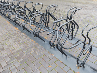 empty bicycle rack or cycle stand at the sidewalk on a rainy day