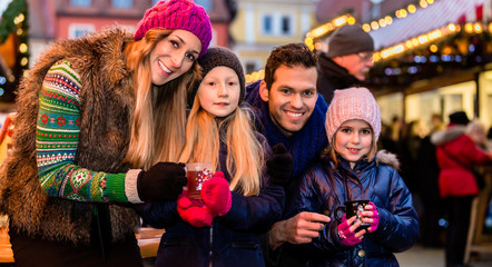 Family drinking mulled wine on Christmas market