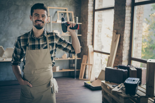 Photo of handsome confident guy master holding electric wireless drill friendly smiling ready to start repair own wooden business industry studio woodwork shop garage indoors