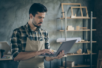 Photo of handsome guy holding notebook watching online video masterclass have free self education focused wooden business industry woodwork shop garage indoors