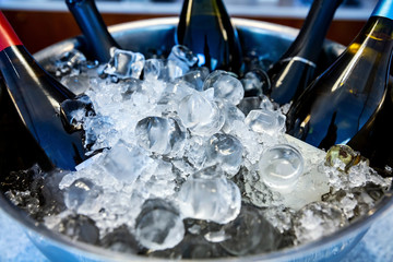 Bottles of wine and champagne, standing in ice bowl on bar counter close up