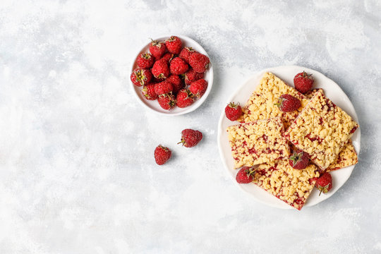 Homemade raspberry crumble bar on plate on light background