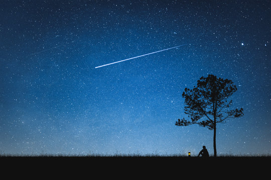 Silhouette of man sitting on mountain and night sky with shooting star. Alone concept.
