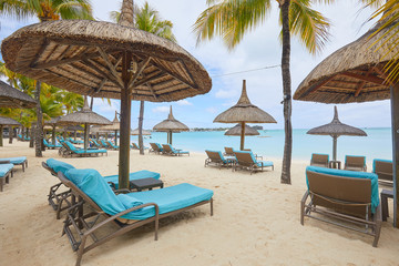 white sand, umbrellas and palm trees on the beach of Mauritius