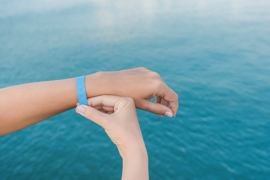 Closeup view of two white hands of woman isolated at blue blurry sea water background. Blue rubber wristband at wrist of one female hand. Horizontal color photography.