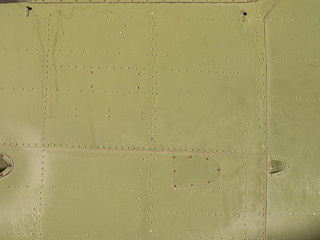 Old green metal surface of the aircraft fuselage with rivets