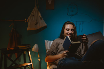 young woman student laying bed in her room and reading book