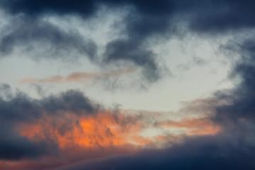Cielo al atardecer con nubes oscuras y anaranjadas.