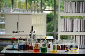Many chemical laboratory glassware and equipment in scientific laboratory room.