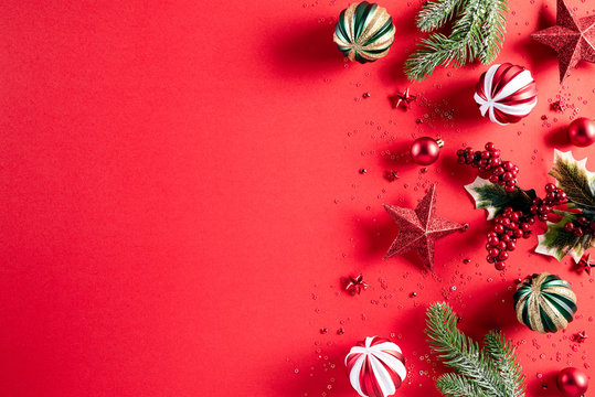 Christmas background concept. Top view of Christmas gift box red balls with spruce branches, pine cones, red berries star and bell on red background.