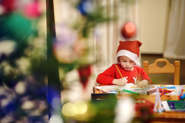 Little boy wearing in a Santa costume is drawing near a decorated Christmas tree.