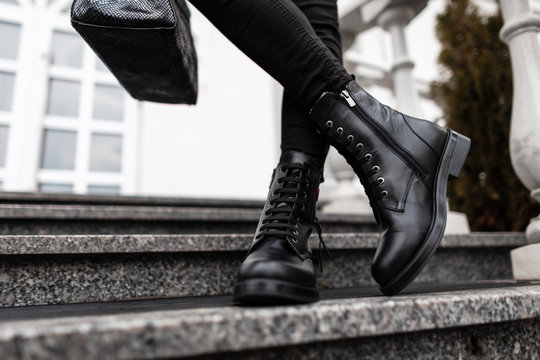 Young trendy woman in stylish leather black boots in jeans with a bag stands on the stone steps in the city. Close up of female legs in fashion footwear. New collection of shoes and accessories.