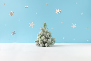 Creative layout with snowy Christmas tree, stars and snowflakes on bright blue background. Minimal...