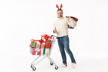 Image of happy man standing by shopping cart with New Year gift boxes