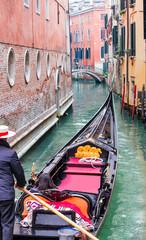 Foto op Canvas Gondolas Venetian gondolier punting gondola through green canal waters of Venice Italy