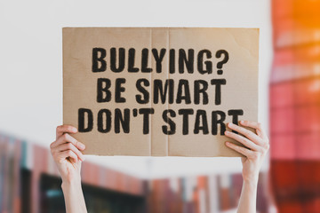 "The phase "" Bulling? Be smart, don't start "" drawn on a carton banner in men's hand. Human holds a cardboard with an inscription. School. University. Childhood. Cruelty"