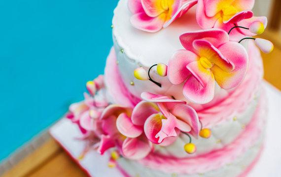 A large pink and white holiday cake decorated with flowers on a wooden tray on the street against the background of water. Copy space