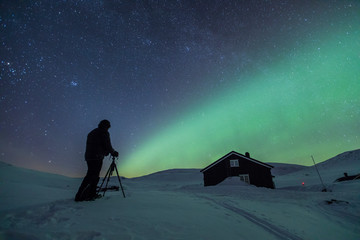 Northern lights and photographer in Reinheim, Dovrefjell National Park, Norway