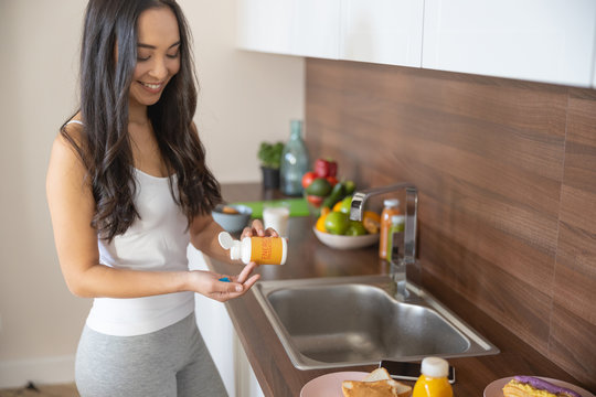 Pleased cute young woman taking energy-boosting vitamins