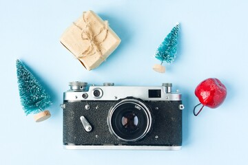 Retro film photo camera, fir trees, apple and cones on blue background. Winter holidays.
