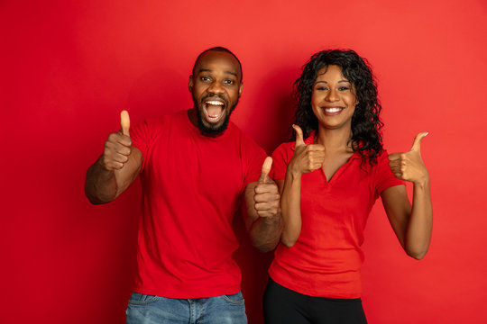 Young emotional african-american man and woman in bright casual clothes posing on red background. Concept of human emotions, facial expession, relations, ad. Couple showing thumbs up and smiling.