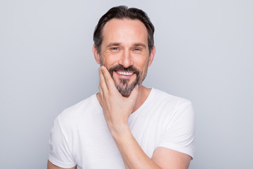 Closeup photo of handsome positive aged man looking mirror toothy smiling hand checking beard after using new shaving gel wear white t-shirt isolated grey color background
