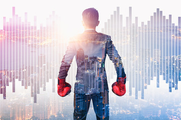 the double exposure image of the businessman wearing a boxing mitts overlay with cityscape image. the concept of fighting, trade war, powerful and business.