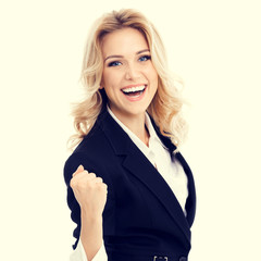 Very happy gesturing businesswoman in confident style black suit. Caucasian blond model in business success concept.