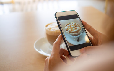 The hand of the woman using a smartphone to take a picture of a coffee in a cafe to post on social media