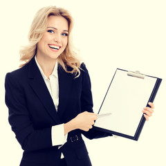 Portrait of young businesswoman in confident style black suit, showing blank clipboard, with copy space for some text or advertise slogan. Blond model in business success concept.